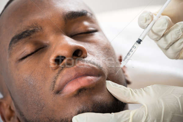 Person Hand Injecting Syringe On Young Man Face Stock photo © AndreyPopov