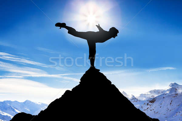 Man Practicing Balancing On A Peak Of A Mountain Stock photo © AndreyPopov