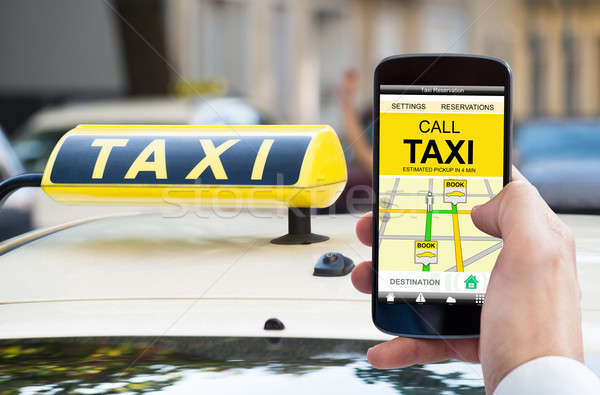 Person's Hand Holding Mobile Phone Booking Taxi Stock photo © AndreyPopov