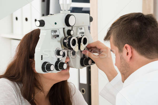 Male Optometrist Adjusting Phoropter While Examining Patient Stock photo © AndreyPopov