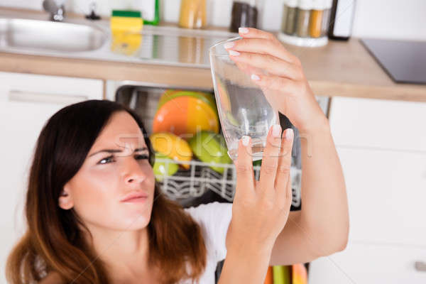 Woman Looking At Glass In Kitchen Stock photo © AndreyPopov