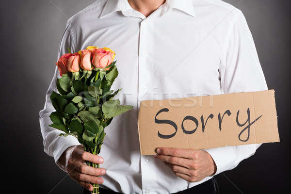 Man Holding Roses And Text Sorry Written On Cardboard Stock photo © AndreyPopov