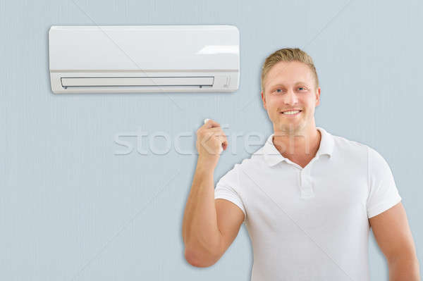 Portret man airconditioner jonge man home huis Stockfoto © AndreyPopov