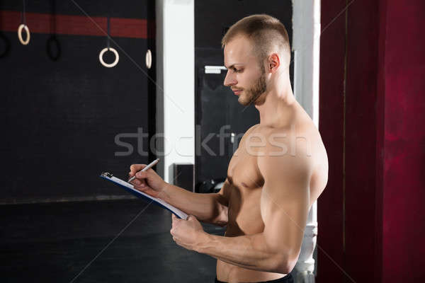 Close-up Of A Person Hand Writing A Workout Plan Stock photo © AndreyPopov