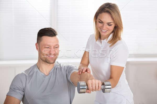Stock photo: Female Physiotherapist Helping Man To Exercise