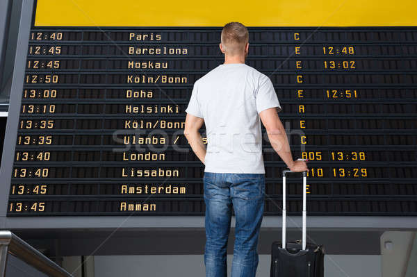 Male Traveler Standing In Front Of Departure Board Stock photo © AndreyPopov