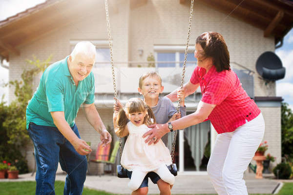Grandparents Looking At Their Grandchildren Playing On Swing Stock photo © AndreyPopov