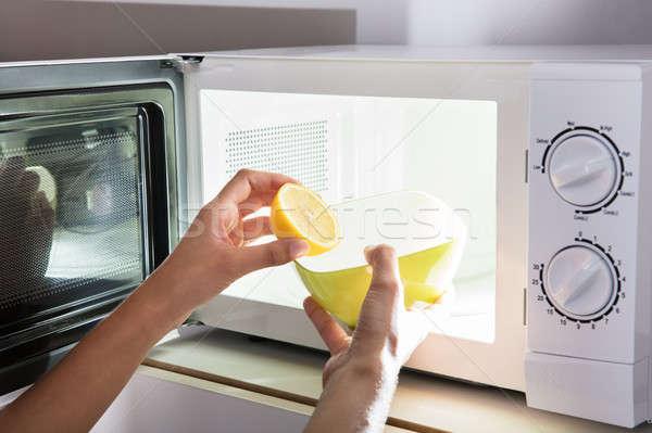 Human Hand Putting Sliced Lemon In Bowl Stock photo © AndreyPopov