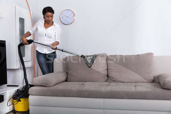 African Woman Cleaning Sofa With Vacuum Cleaner Stock photo © AndreyPopov