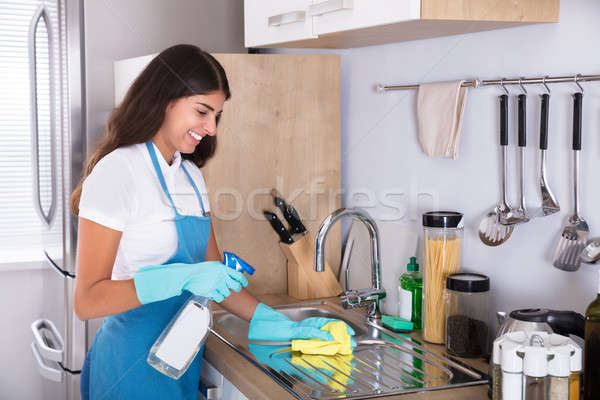 Woman Cleaning Kitchen Sink With Yellow Cloth And Spray Stock photo © AndreyPopov
