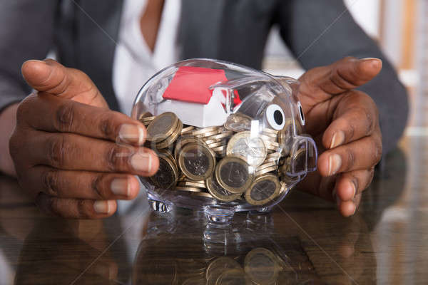 Menselijke hand bescherming spaarvarken huis model munten Stockfoto © AndreyPopov