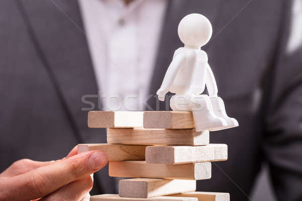 Human Figure Sitting On Top Of Stacked Wooden Blocks Stock photo © AndreyPopov