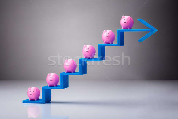 Stock photo: Many Pink Piggybanks On Blue Arrow Steps