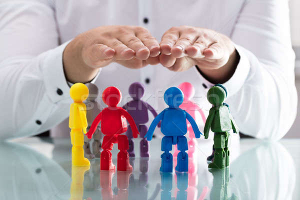Person protecting multi colored human figures Stock photo © AndreyPopov