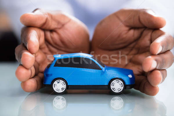 Businessman's Hand Protecting Blue Toy Car Stock photo © AndreyPopov