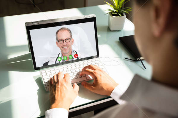 Businessman videoconferencing with doctor on laptop Stock photo © AndreyPopov