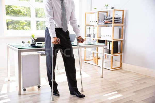 Niepełnosprawnych biznesmen kule kalekiego stałego biuro okno Zdjęcia stock © AndreyPopov