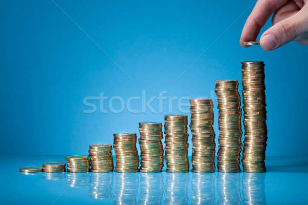 Hand Placing Coin On Stack Of Coins Stock photo © AndreyPopov