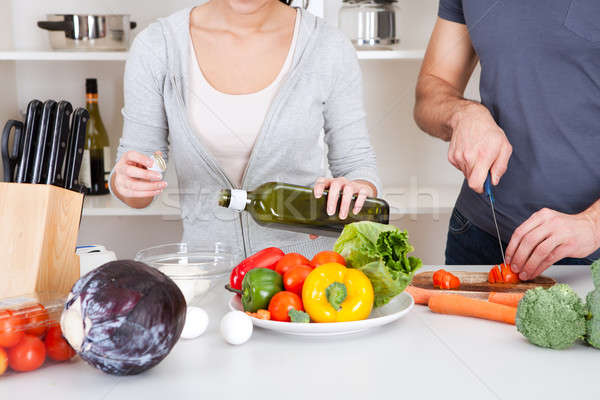 Stock photo: Adding olive oil while cooking salad