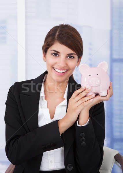 Happy Businesswoman Holding Piggybank In Office Stock photo © AndreyPopov