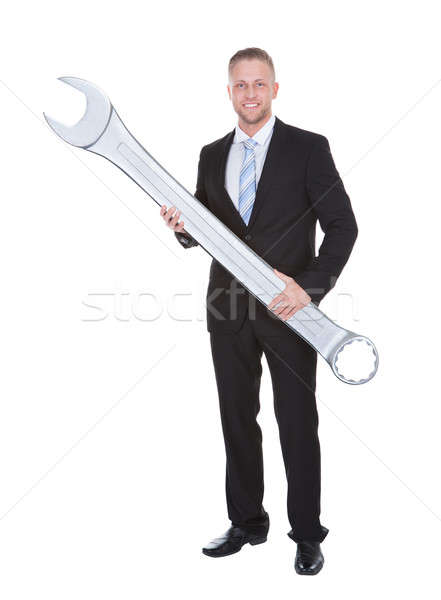 Businessman in a smart suit holding a large metal spanner Stock photo © AndreyPopov