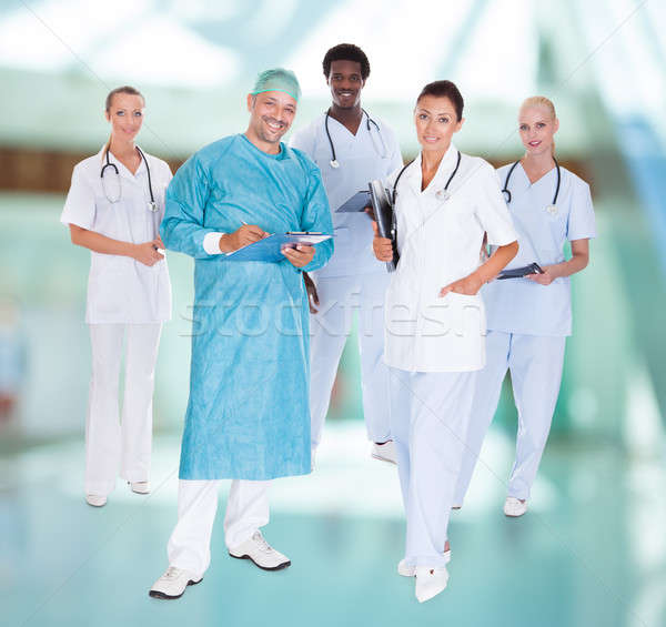 Happy Doctor In Surgical Gown With His Coworkers Stock photo © AndreyPopov