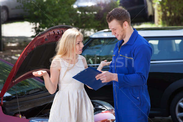 Stock photo: Mechanic Showing Clipboard To Angry Woman By Breakdown Car