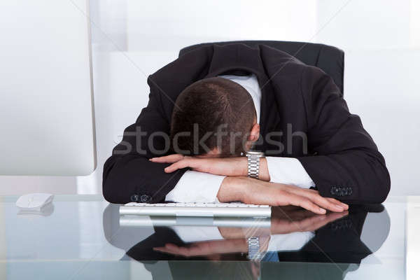 Tired Businessman Sitting At Computer Desk Stock photo © AndreyPopov