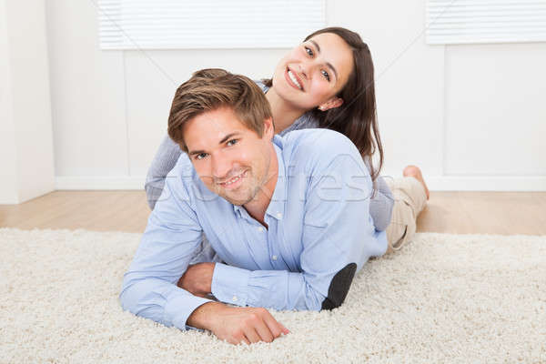 Loving Couple Lying On Rug In Living Room Stock photo © AndreyPopov