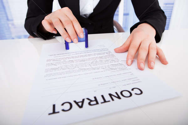 Businesswoman Using Corporate Seal On Contract Paper Stock photo © AndreyPopov