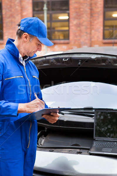 Automotive Mechanic Writing On Clipboard Stock photo © AndreyPopov
