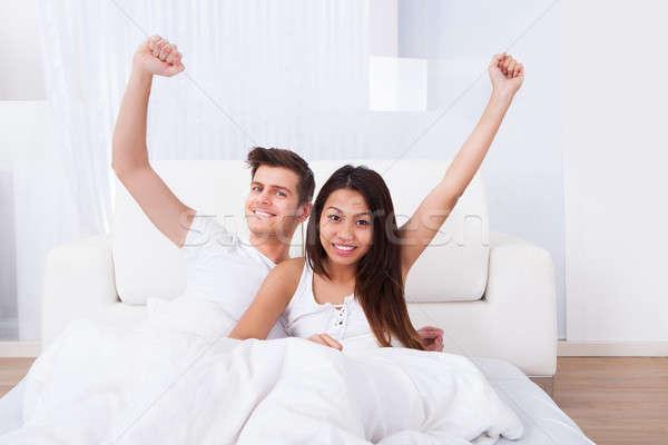 Boldog pár karok a magasban ül matrac portré Stock fotó © AndreyPopov