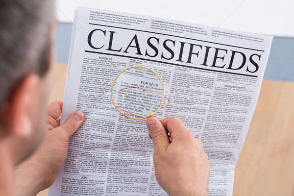 Man Looking Classifieds Through Magnifying Glass Stock photo © AndreyPopov