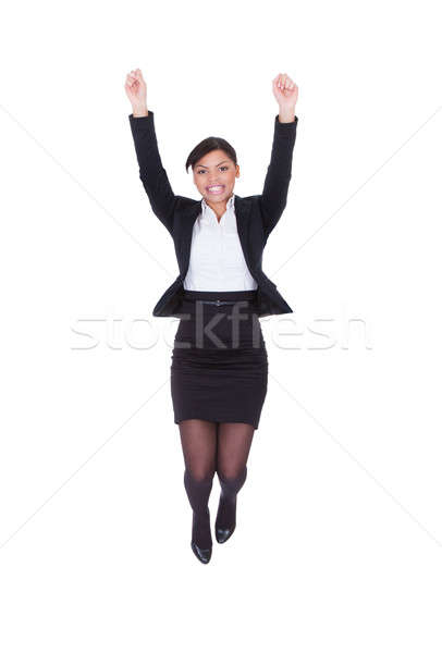 Businesswoman Jumping With Arms Raised Stock photo © AndreyPopov