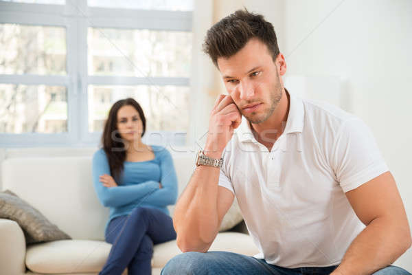 Defocused Woman In Front Of Sad Young Man Stock photo © AndreyPopov