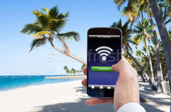 Persoon hand wifi mobiele telefoon strand Stockfoto © AndreyPopov