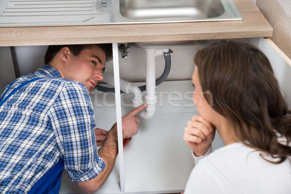 Plumber Showing Damage In Sink Pipe To Woman  Stock photo © AndreyPopov