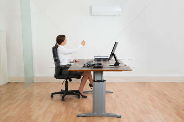 Businesswoman Using Air Conditioner In Office Stock photo © AndreyPopov