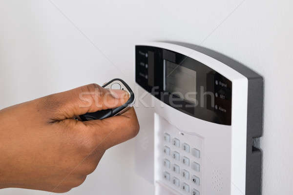 Person's Hand Using Remote To Operate Entrance Security System Stock photo © AndreyPopov