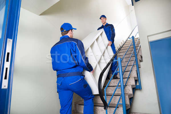 Movers Carrying Shelf While Climbing Steps At Home Stock photo © AndreyPopov