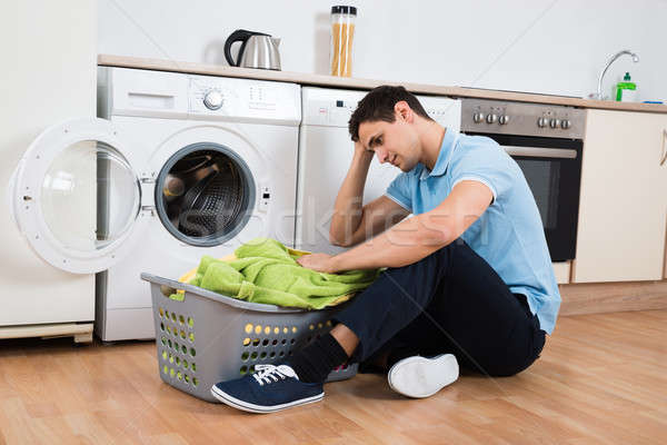 Tensed Man Looking At Laundry Basket By Washing Machine Stock photo © AndreyPopov