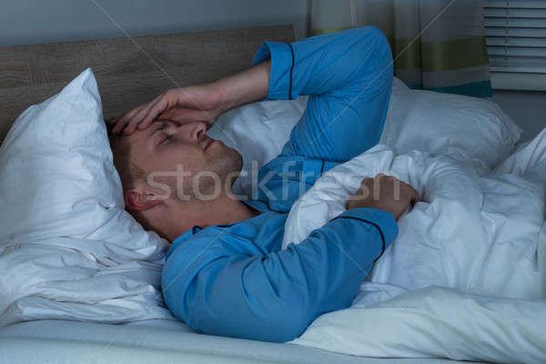 Człowiek cierpienie głowy bed młody człowiek sypialni Zdjęcia stock © AndreyPopov