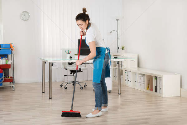 Female Janitor Sweeping Floor With Broom Stock photo © AndreyPopov