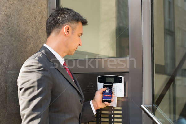 Businessman Disarming Security System Of Door With Smartphone Stock photo © AndreyPopov