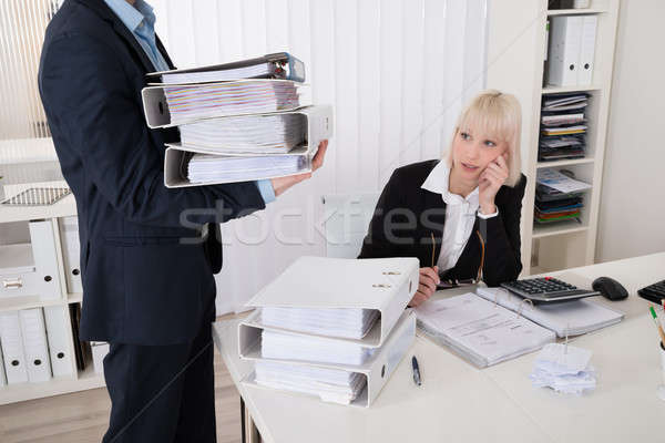 Businessman Giving Pile Of Folders To Female Assistant Stock photo © AndreyPopov
