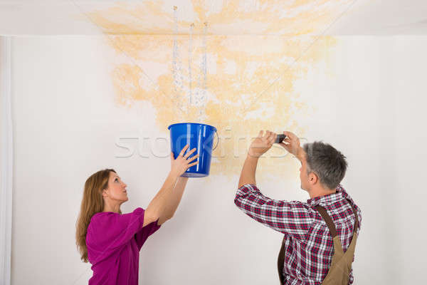 Man Photographing While Woman Collecting Water From Ceiling Stock photo © AndreyPopov