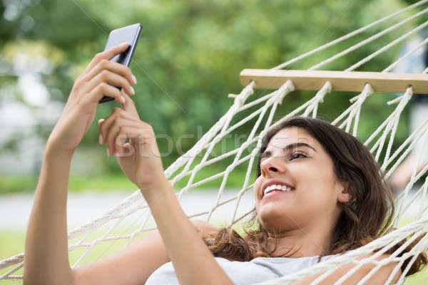 Woman Relaxing In Hammock Using Mobile Phone Stock photo © AndreyPopov