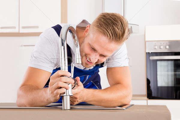 Plombier robinet cuisine heureux jeunes Photo stock © AndreyPopov