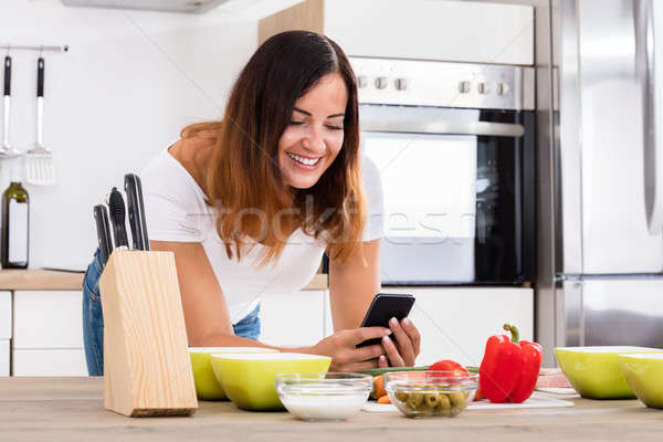 Smiling Woman Using Smartphone In Kitchen Stock photo © AndreyPopov