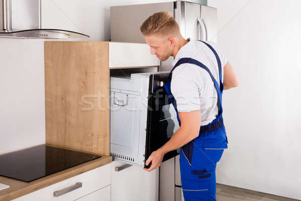 Technician Repairing Oven In Kitchen Stock photo © AndreyPopov